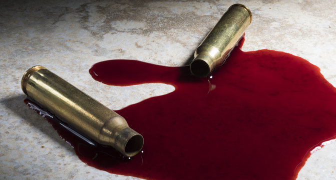 Two empty rifle cartridges on the floor with blood