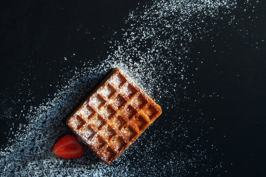 Belgian waffles with strawberry and powdered sugar.