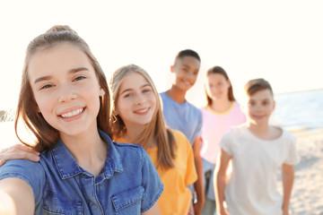 Group of children taking selfie on beach. Summer camp