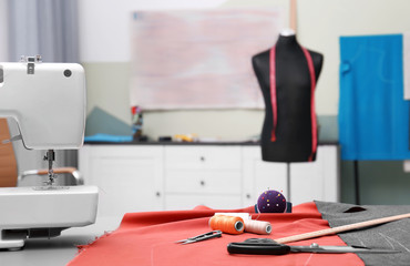 Fabric and sewing tools on table in tailor workshop