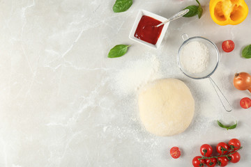 Dough and ingredients for pizza on light background, top view