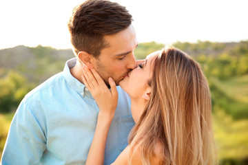 Cute young couple in love posing outdoors on sunny day