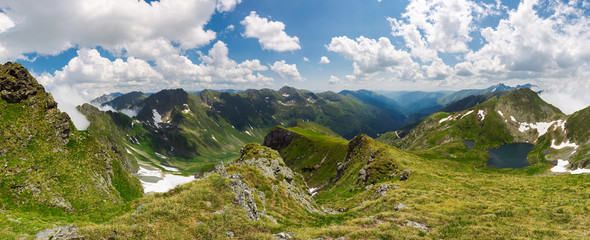 panorama of Fagaras mountain ridge in summer. beautiful view in to the valley of beautiful landscape with gorgeous cloudscape. rocky cliffs above the grassy slopes with some snow.