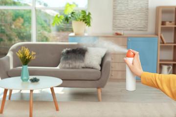 Fototapeta Woman spraying air freshener at home