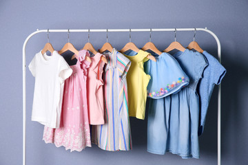 Rack with stylish child clothes on color background
