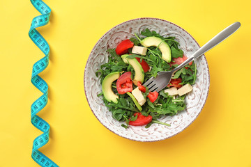 Bowl with fresh vegetable salad and measuring tape on color background, top view. Healthy diet