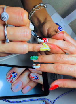 Russian manicurist Natalia paints her friend Katya's nails with flags of teams and themes of the 2018 Soccer World Cup in her apartment in central Samara
