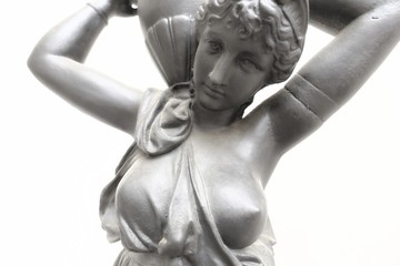 Detail of the face and breast of the cast iron statuete of the girl