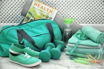 Sports bag and gym equipment in different mint color shades on floor