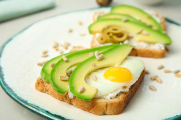Crisp toast with avocado and quail egg on plate, closeup