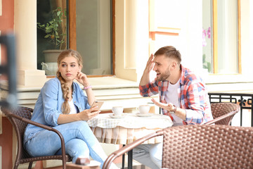 Young couple arguing while sitting in cafe, outdoors. Problems in relationship