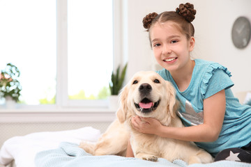 Cute little child with her pet on bed at home