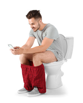 Young man using mobile phone while sitting on toilet bowl. Isolated on white