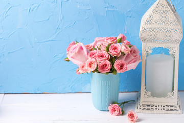 Background with pink roses flowers in blue cup  and white lantern with candle against  blue textured wall.