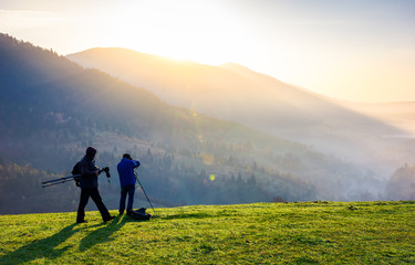 photographers on workshop at sunrise. capturing gorgeous scenery of mountainous area from the top of grassy hill. beautiful landscape with sun rising behind the forested mountain and foggy valley