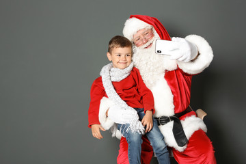 Authentic Santa Claus taking selfie with little boy on grey background