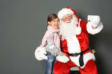 Authentic Santa Claus taking selfie with little girl on grey background