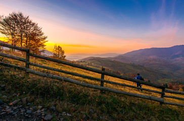 photographer on workshop at dawn in mountains. capturing gorgeous scenery of beautiful landscape with sun rising behind the forested mountain and foggy valley under the gorgeous reddish sky