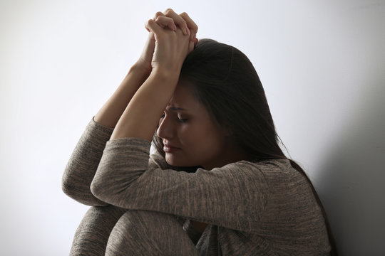Depressed young woman sitting near light wall