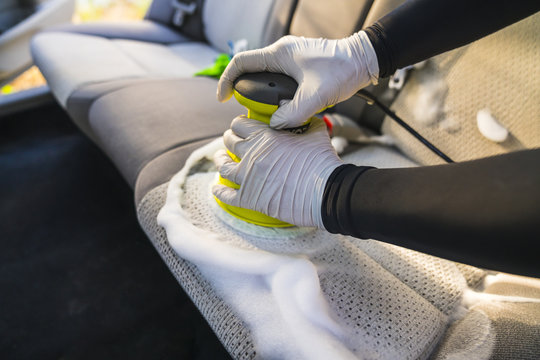 a man cleaning car interior by use foam chemical  and scrubbing machine.