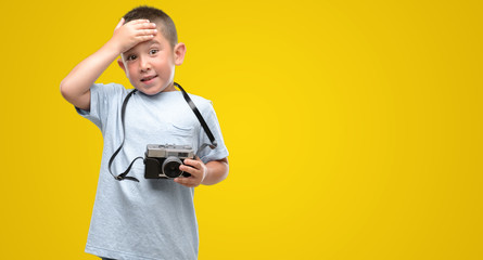 Dark haired little child holding vintage camera stressed with hand on head, shocked with shame and surprise face, angry and frustrated. Fear and upset for mistake.