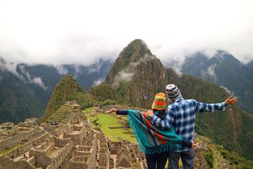 Couple admiring the spectacular view of Machu Picchu, UNESCO World Heritage site in Cusco Region, Urubamba Province, Peru