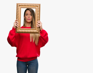 Beautiful young woman holding vintage frame with a confident expression on smart face thinking serious