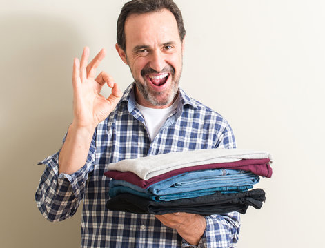 Senior man holding folded laundry clothes doing ok sign with fingers, excellent symbol