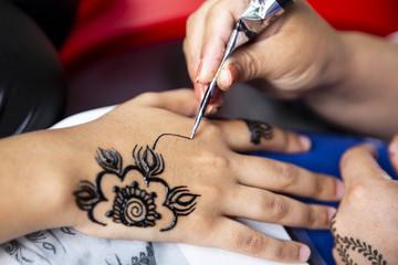 Applying henna tattoo