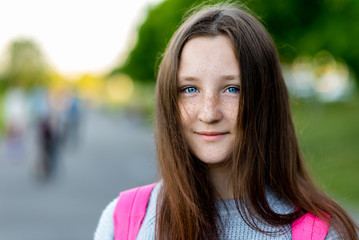 A beautiful child, teenage girl. Summer in nature. Close-up portrait. Blue eyes freckles on face. Smiles happily. Free space for text. Concept of rest. Emotion of pleasure.
