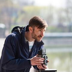 bearded photographer photographs with enthusiasm the film camera.