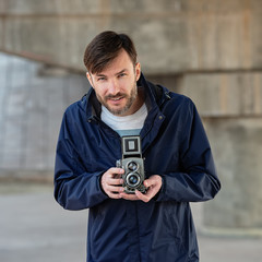 bearded photographer photographs with enthusiasm the film camera.
