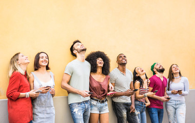 Multiracial friends having fun using smartphone at wall on university college break - Young people addicted by mobile smart phones - Technology concept with always connected millennials - Filter image