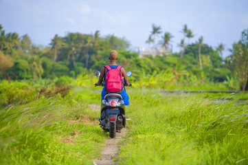 young attractive tourist afro American black woman riding motorbike  happy in beautiful Asia countryside along green rice fields smiling free on her scooter