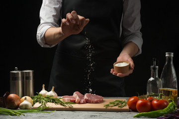Pork steak and salt by the chef on the background. Horizontal photo. With vegetables, tomatoes, hot peppers, onions and chasnok. With black background