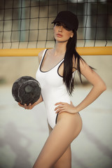 Sportive woman with sexy body is wearing white fashion swimsuit and black hat is playing beach volleyball, summer vacations