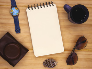 Blank page of spiral notepad on wooden table. Summer travel flat lay photo. Empty sketchbook page on table top view.