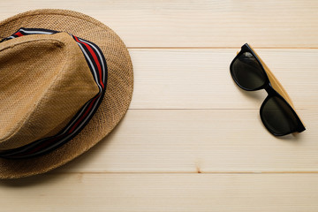 Top view and close up: Brown hat and sunglasses on wooden table background. Summer season, beach vacation concept.