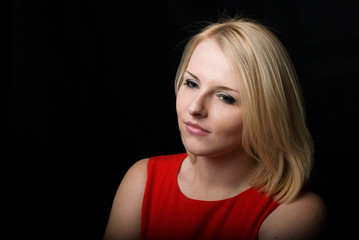 Photo of the girl of the blonde in a red dress with a thoughtful look. Black background.