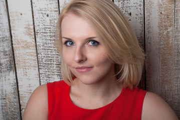 Photo of the girl of the blonde in a red dress on a wooden background.