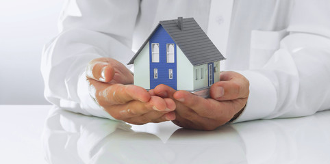 Business man is holding a detached house