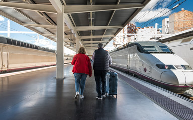 The elderly couple on the railway platform goes on a trip