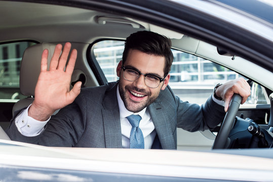 side view of cheerful businessman greeting someone while driving car
