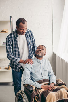 adult african american son looking at disabled senior father in wheelchair