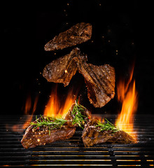 Flying beef steaks on grill with Fire flames