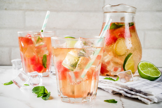 Iced watermelon and lime green tea with mint leaves, marble white background copy space