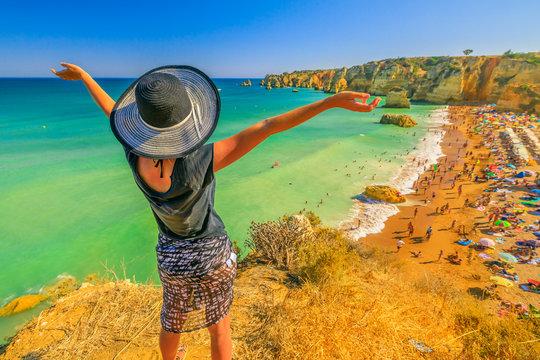 Tourism in Portugal. Lifestyle female tourist on promontory of Praia Dona Ana, Portugal. Caucasian freedom woman enjoying at Dona Ana Beach in Lagos on Algarve coast. Summer holidays in Europe.
