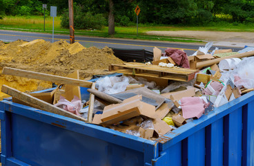 Blue construction debris container filled with rock and concrete rubble. Industrial garbage bin