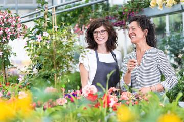 Floristin lachend mit Kundin im Gewächshaus