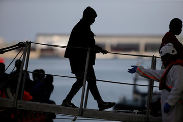 Migrants women leave a rescue boat upon arrival at the port of Malaga